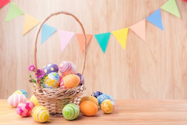 Le uova variopinte e i fiori del giorno felice di pasqua nel canestro e nel coniglio sul pavimento di legno hanno offuscato celebrano le bandiere del partito con lo spazio della copia