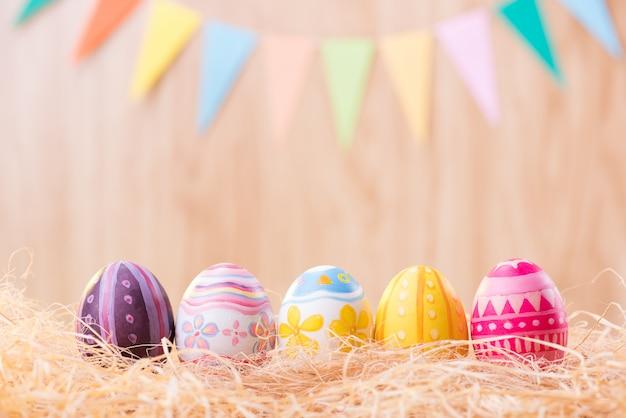 Le uova variopinte felici del giorno di pasqua sul nido con vago celebrano le bandiere del partito con lo spazio della copia