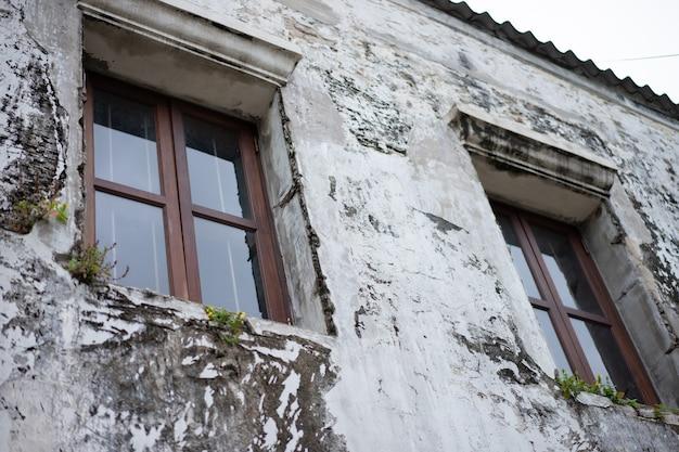 Le vecchie finestre marroni e di legno si trovano sul muro dell'antica casa.