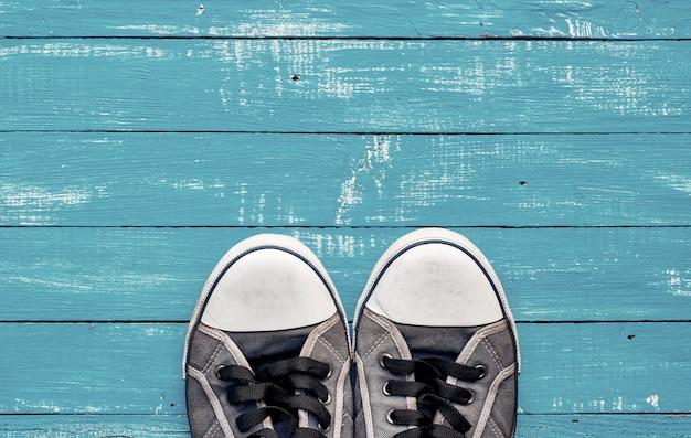 Le vecchie scarpe da tennis misere degli uomini blu su una superficie di legno blu