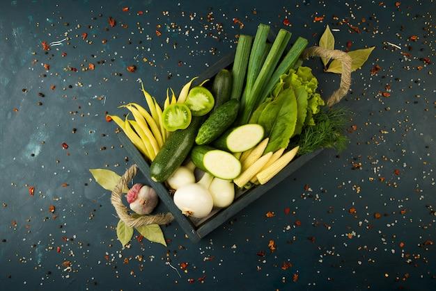 Le verdure nella scatola sulla pietra uno scuro. giovani cipolle di erbe fagioli verdi all'aglio giallo di mais zucchini le spezie luminose sono in una scatola di legno con maniglie a corda su uno scuro strutturato.