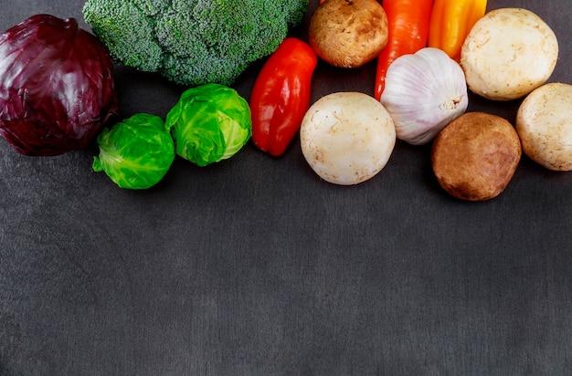 Le verdure organiche fresche disposte delle verdure di legno scure del fondo hanno incluso nella composizione dallo spazio del testo.