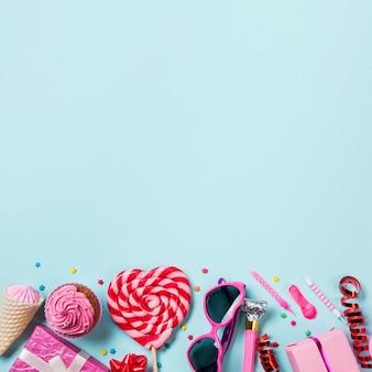 Lecca-lecca a forma di cuore; muffin; cono; pacco regalo; palloncino; candela; streamer e scatole regalo sullo sfondo blu