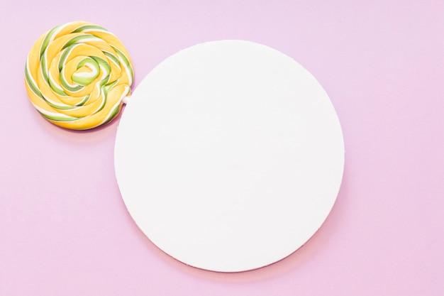 Lecca-lecca a strisce gialla e verde sopra la struttura circolare bianca contro fondo rosa