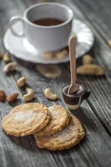 Lecca lecca al cioccolato a forma di piccola tazza con una tazza di tè e noci su legno