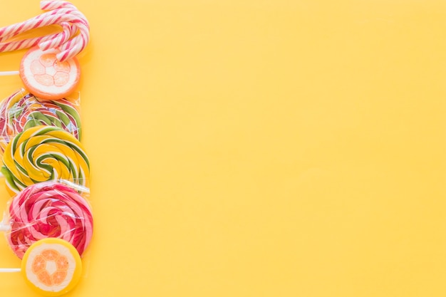 Lecca-lecca colorate e caramelle di canna di natale su sfondo giallo