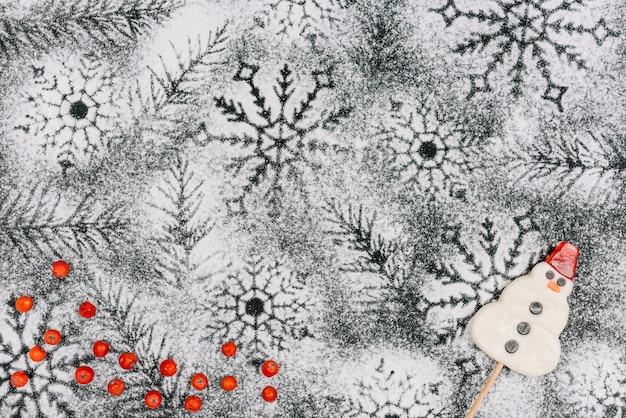 Lecca lecca di pupazzo di neve su fiocchi di neve in polvere di zucchero