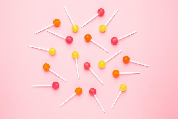 Lecca-lecca rosa, arancio e gialla della caramella dolce sul rosa pastello
