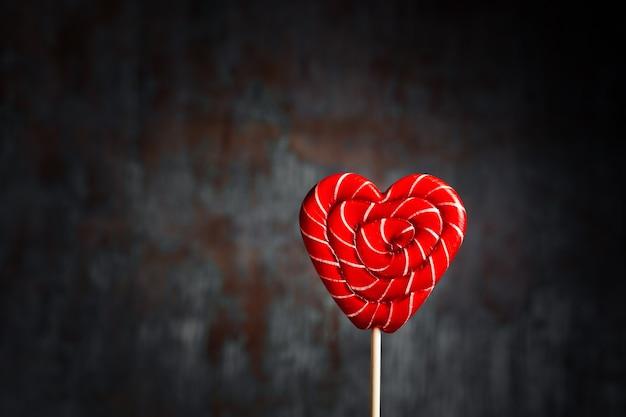 Lecca-lecca rossa a forma di cuore su uno sfondo scuro con spazio di copia