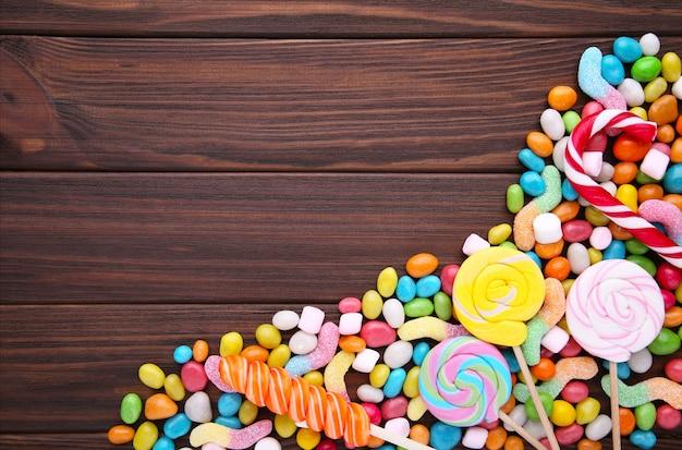 Lecca-lecca variopinte e caramella rotonda colorata differente sulla tavola marrone