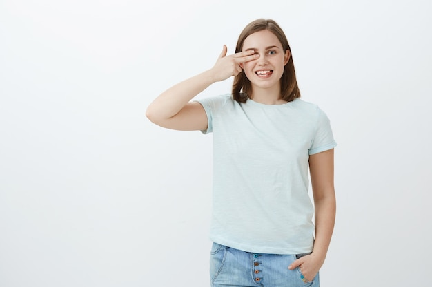 Leggere le parole con un occhio solo nel negozio di ottica, raccogliendo nuovi occhiali. ritratto di donna affascinante gioiosa dall'aspetto amichevole con capelli castani corti che tengono le dita a vista che puntano a destra e sorridono gioiosamente