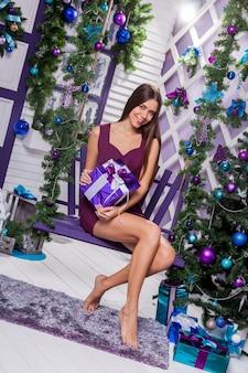 Leggy bruna in un abito turchese seduto su un'altalena viola