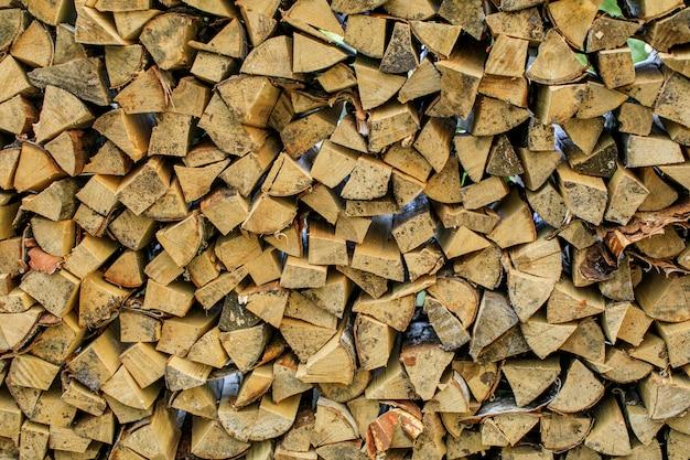 Legna da ardere da parete, sfondo di legna da ardere secca tritata registra in una pila. foto di alta qualità