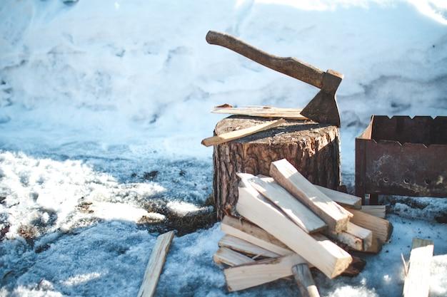 Legna da ardere e ascia vicino al barbecue. vacanze invernali