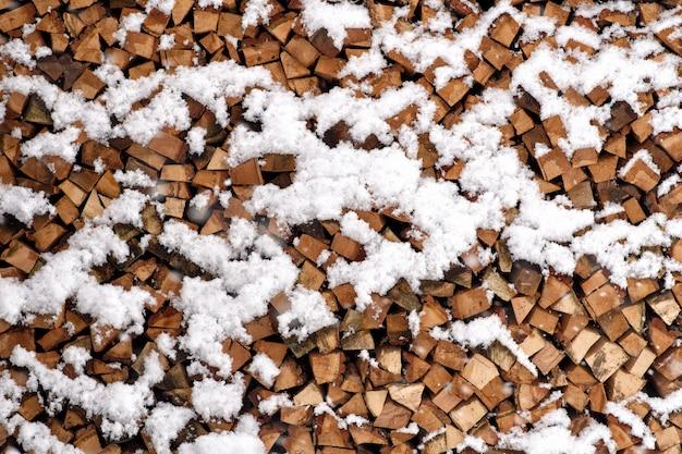 Legna da ardere tagliata piegata coperta di neve in inverno