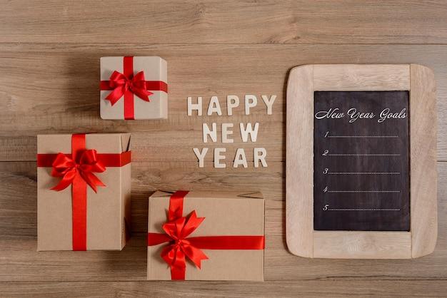 Legno di felice anno nuovo e lista degli obiettivi di capodanno scritti sulla lavagna con scatola regalo