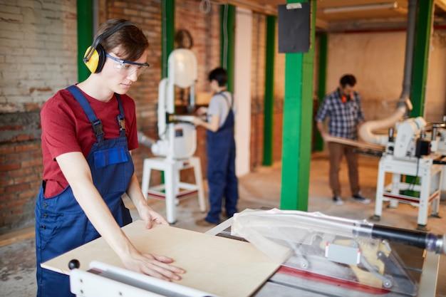 Legno di taglio del giovane operaio alla fabbrica