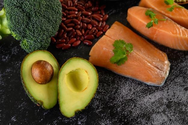 Legumi, broccoli, frutta e salmone posti su un pavimento di cemento nero.