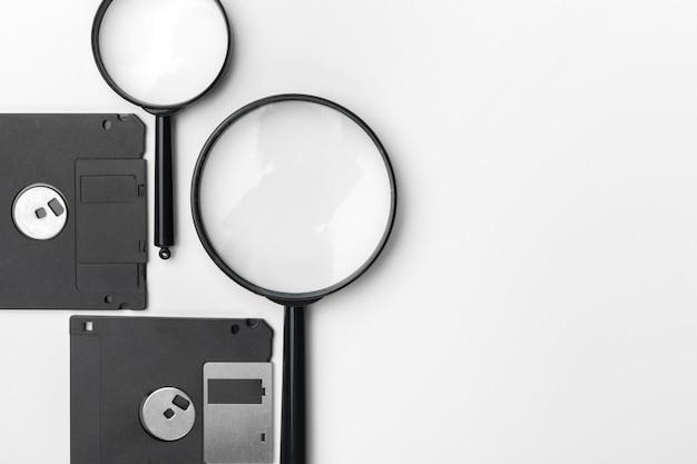 Lente d'ingrandimento che ispeziona sul concetto di floppy disk