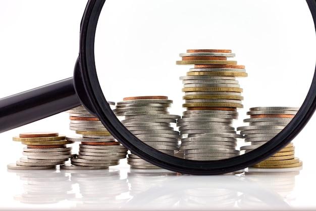 Lente d'ingrandimento con un mucchio di monete, finanza di concetto e attività bancarie