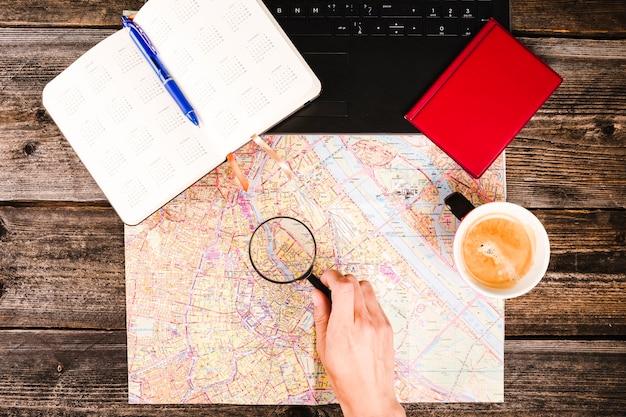 Lente d'ingrandimento della tenuta del viaggiatore sopra la mappa oltre a caffè e diario sul tavolo