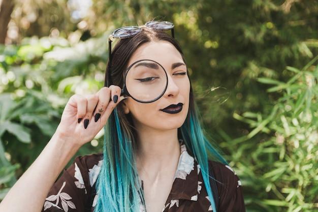 Lente d'ingrandimento della tenuta della giovane donna sopra l'un occhio