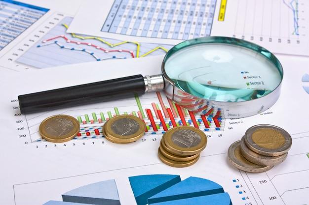 Lente d'ingrandimento e il documento di lavoro con le monete