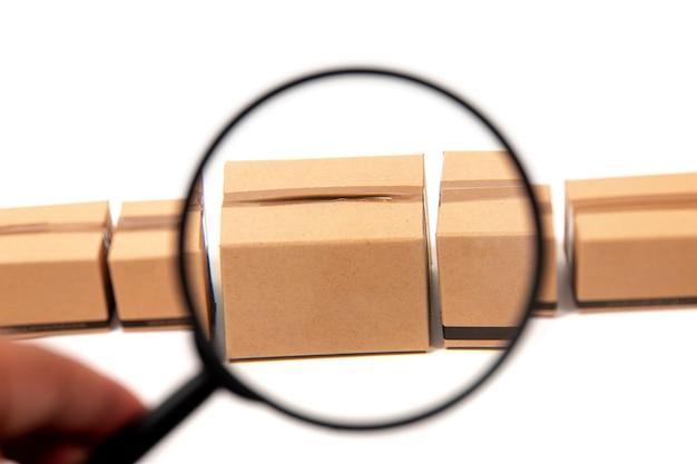 Lente d'ingrandimento ispezionando una scatola di cartone.