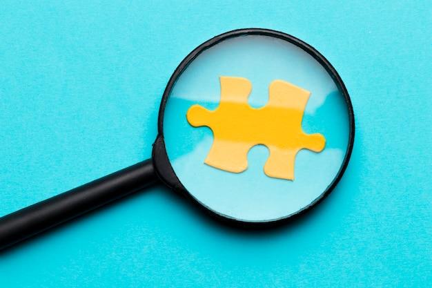 Lente d'ingrandimento sopra il pezzo di puzzle giallo su sfondo blu