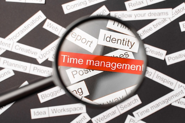 Lente d'ingrandimento sopra la gestione del tempo di iscrizione rossa ritagliata di carta