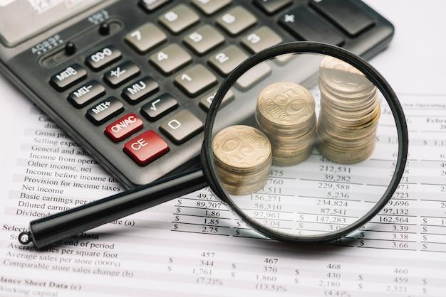 Lente d'ingrandimento sopra la pila di monete e calcolatrice sul rapporto finanziario