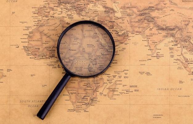 Lente d'ingrandimento sulla mappa d'epoca. concetto di viaggio e avventura.