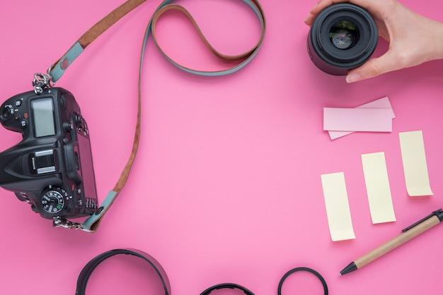 Lente della macchina fotografica della holding della mano della persona con la macchina fotografica e le note appiccicose; penna su sfondo rosa