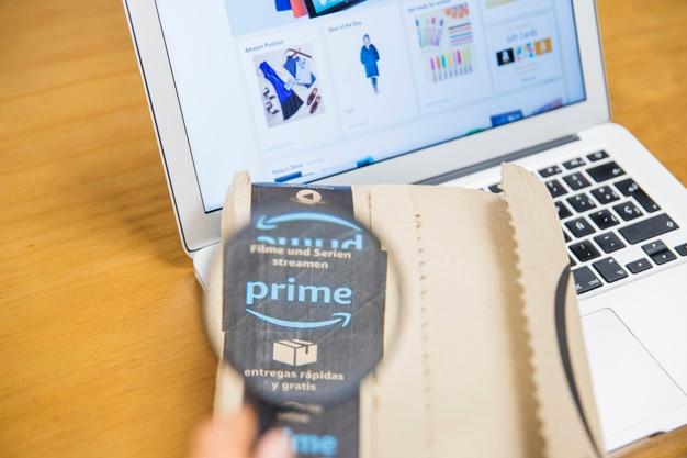 Lente e consegna femminili della tenuta della mano vicino al computer portatile