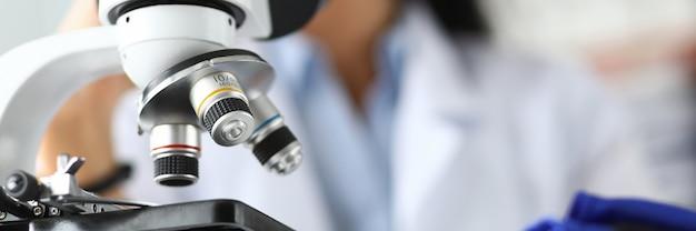 Lente microscopio scientifico con analista femmina in background