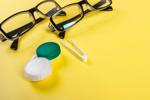 Lenti a contatto con custodia in plastica e pinzette con gli occhiali sul piano di sfondo su uno sfondo lilla