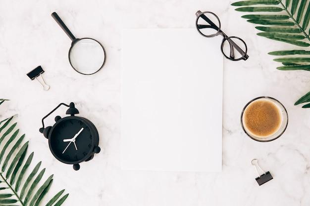 Lenti d'ingrandimento; sveglia; occhiali; caffè; clip di bulldog e foglie con carta bianca vuota su sfondo texture marmo