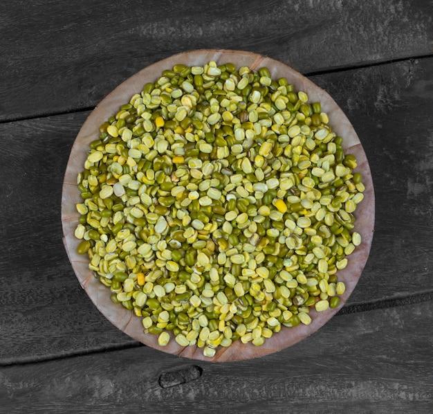 Lenticchie spaccate crude del fagiolo verde o mung daal su fondo di legno