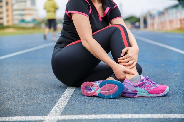 Lesione e dolore alla caviglia dell'atleta corridore femminile. donna che soffre di dolorosa caviglia mentre corre sulla pista da corsa gommata blu.