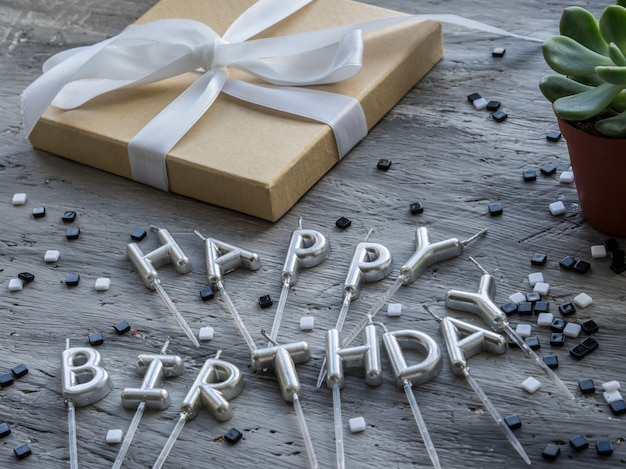 Lettera buon compleanno dalle candele su sfondo grigio. concetto di buon compleanno