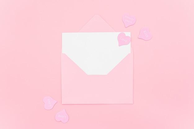 Lettera d'amore. busta rosa con la carta in bianco bianca e cuori sul rosa