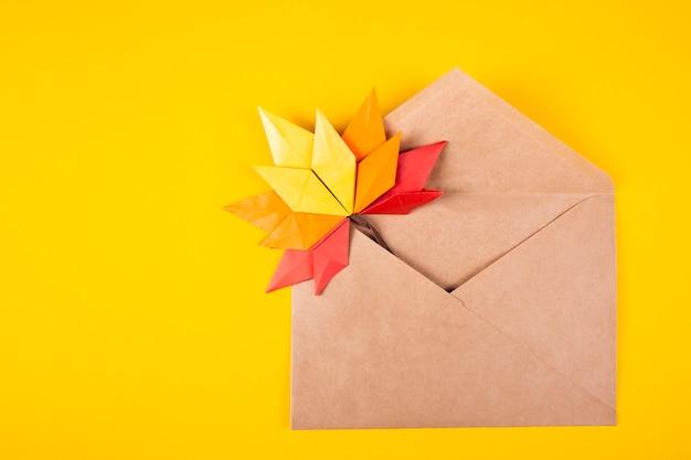 Lettera delle foglie cadute di concetto di autunno del papercraft di origami in una busta su un'arte artigianale fatta a mano del fondo normale
