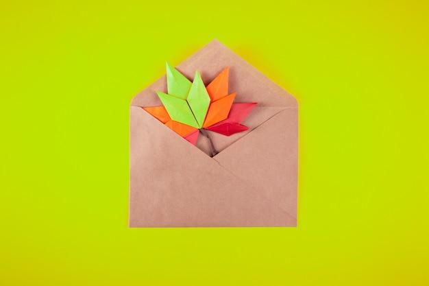 Lettera delle foglie cadute di concetto di autunno del papercraft di origami in una busta su un topshot fatto a mano di arte del mestiere del fondo normale