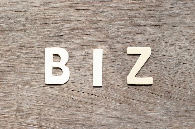 Lettera di alfabeto in parola biz (abbreviazione di business) su legno