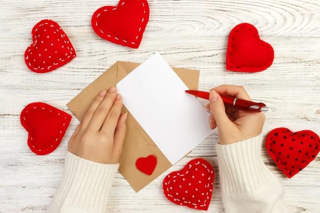 Lettera di amore di scrittura della donna sulla cartolina d'auguri in bianco