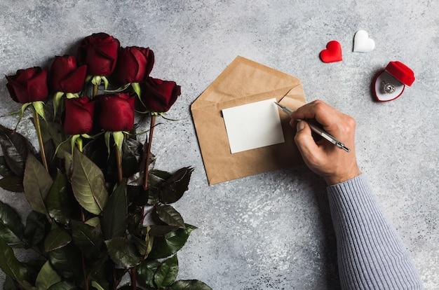 Lettera di amore di scrittura della penna di tenuta della mano dell'uomo di giorno di biglietti di s. valentino con la cartolina d'auguri
