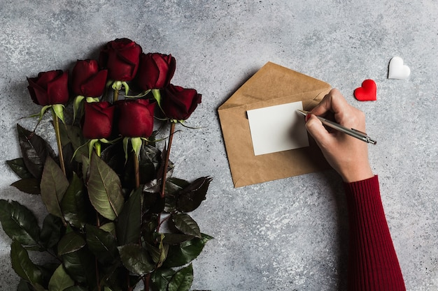 Lettera di amore di scrittura della penna di tenuta della mano della donna di giorno di biglietti di s. valentino con la cartolina d'auguri