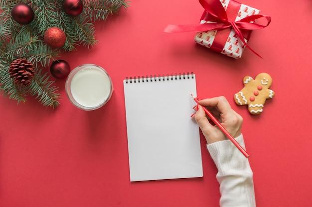 Lettera di natale per babbo natale con latte, biscotti, panpepato su rosso. vista dall'alto e spazio per il testo. disteso.