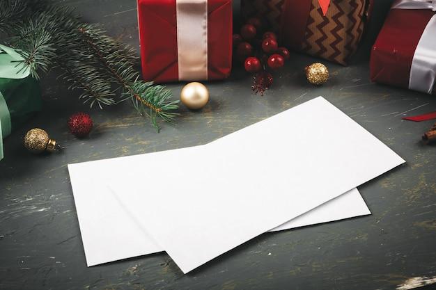 Lettera di saluto, busta e piuma circondata da decorazioni natalizie