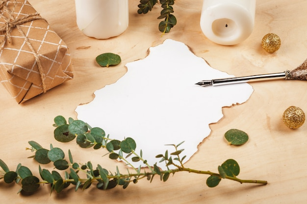Lettera stagionale con una penna d'oca piuma d'annata su fondo di legno